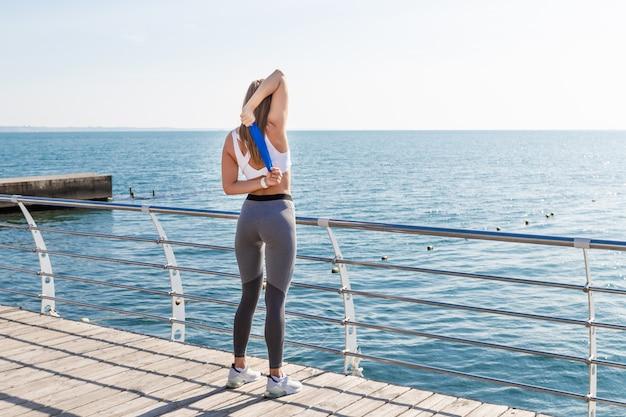 Garota esportiva no sportswear fazendo exercícios de alongamento.
