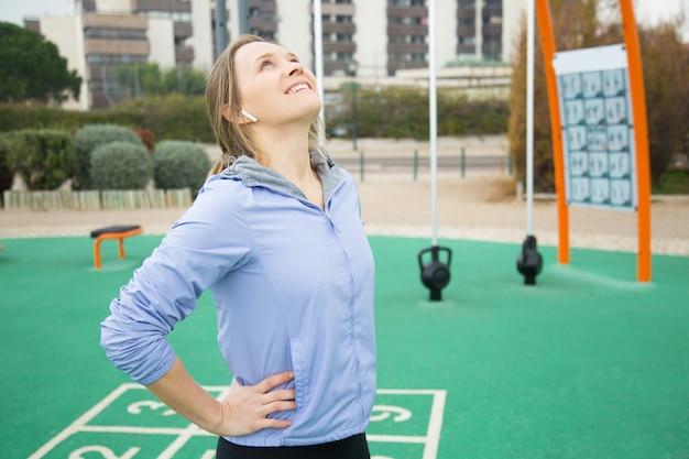Garota esportiva positiva, aquecendo o pescoço