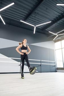 Garota esportiva praticando saltos de canguru dentro de casa