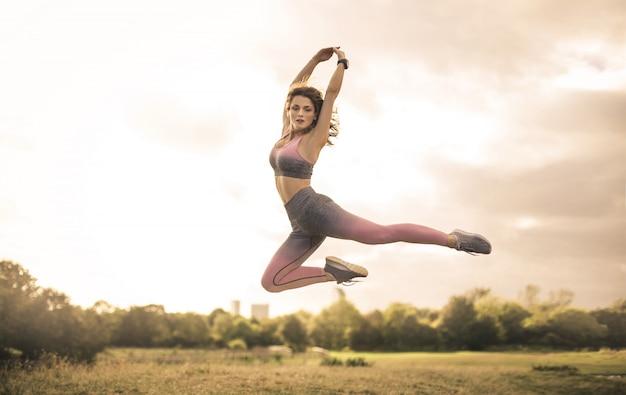 Garota esportiva pulando em um campo