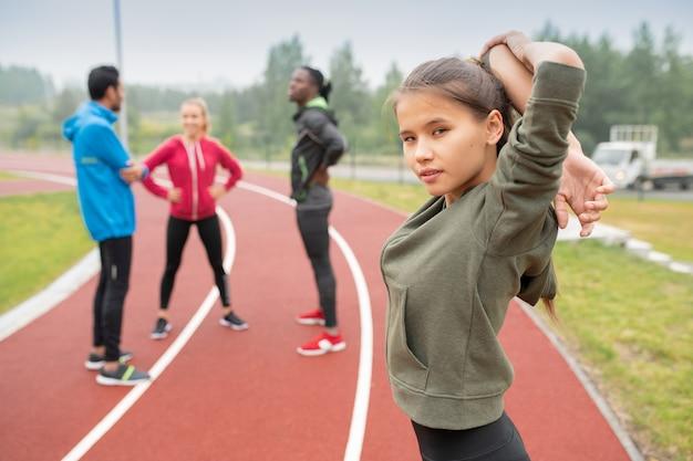 Garota esportiva vestindo roupas esportivas se preparando para a maratona enquanto faz exercícios de aquecimento no estádio
