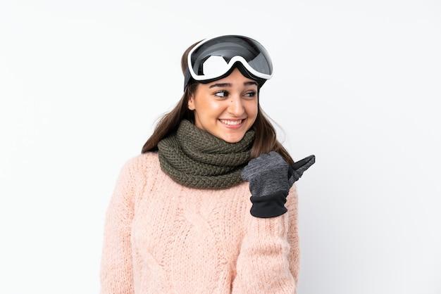 Garota esquiador com óculos de snowboard apontando para o lado para apresentar um produto