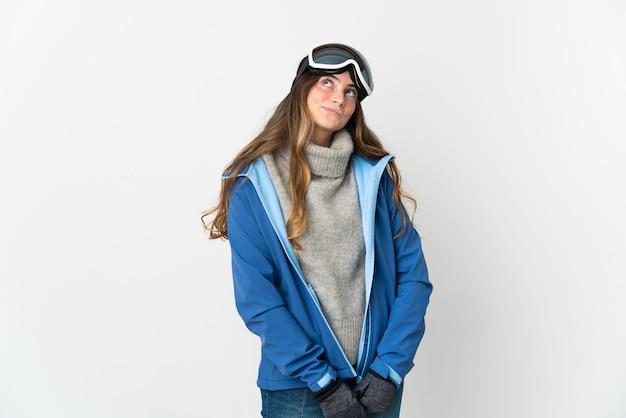 Garota esquiadora com óculos de snowboard isolados no fundo branco e olhando para cima