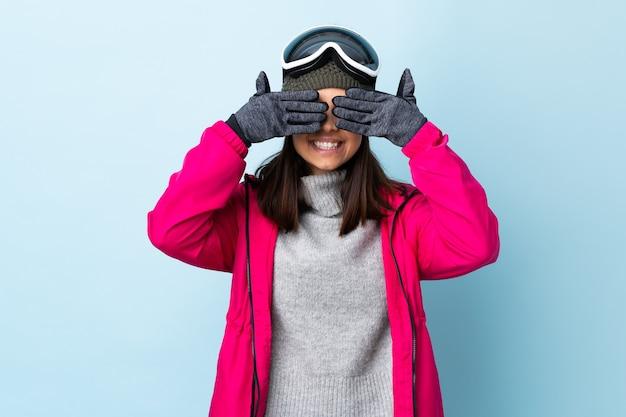 Garota esquiadora de raça mista com óculos de snowboard sobre fundo azul isolado, cobrindo os olhos pelas mãos e sorrindo.