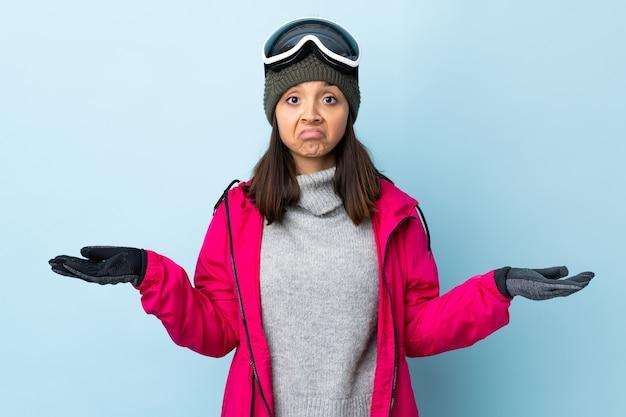 Garota esquiadora de raça mista com óculos de snowboard sobre fundo azul isolado, tendo dúvidas ao levantar as mãos.