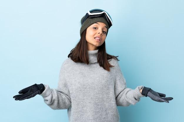 Garota esquiadora de raça mista com óculos de snowboard sobre fundo azul isolado, tendo dúvidas.