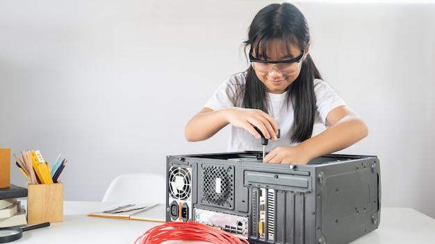 Garota está consertando o hardware do computador na mesa de trabalho branca moderna.
