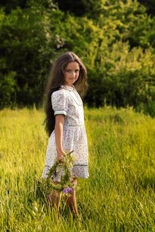 Garota está de pé na grama verde, ela fez uma coroa de flores.