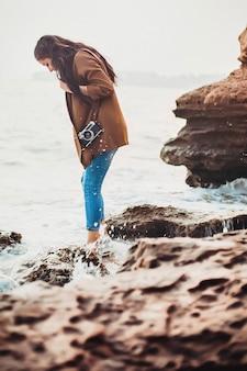 Garota está de pé na praia sobre as pedras e olhando para as ondas