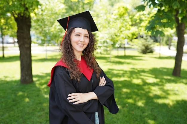 Garota está de pé no parque verde perto da universidade