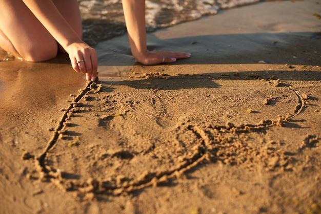 Garota está desenhando um coração na areia à beira-mar à noite com os dedos