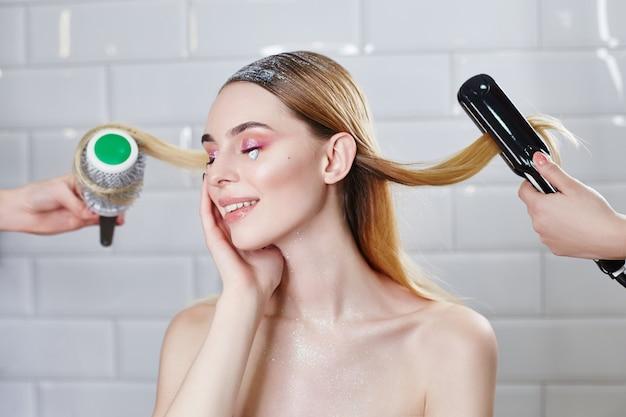 Garota está fazendo o cabelo em um salão de beleza, penteado e penteado.
