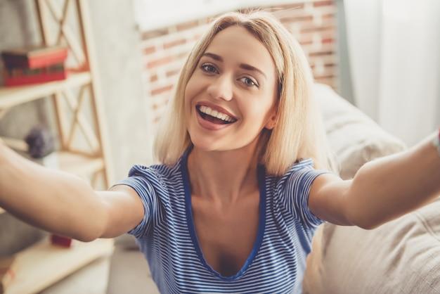 Garota está fazendo selfie e sorrindo enquanto está sentado no sofá