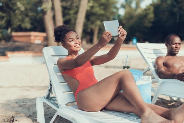 Garota está fazendo selfie no tablet pc. dia ensolarado na praia