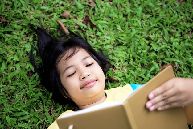 Garota está lendo um livro no gramado.