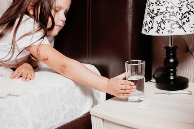 Garota está pegando um copo d'água na mesa de cabeceira