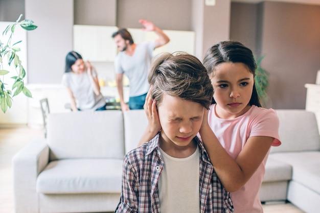 Garota está por trás de seu irmão e mantém os ouvidos fechados com as mãos. o menino está aterrorizado. ele tem os olhos fechados. mulher está tentando se proteger. o cara vai vencê-la. ele levanta a mão.