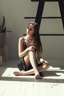 Garota está posando em um estúdio de luz com pérolas no rosto