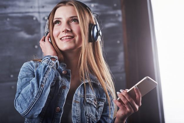 Garota está posando no estúdio ouve música em fones de ouvido