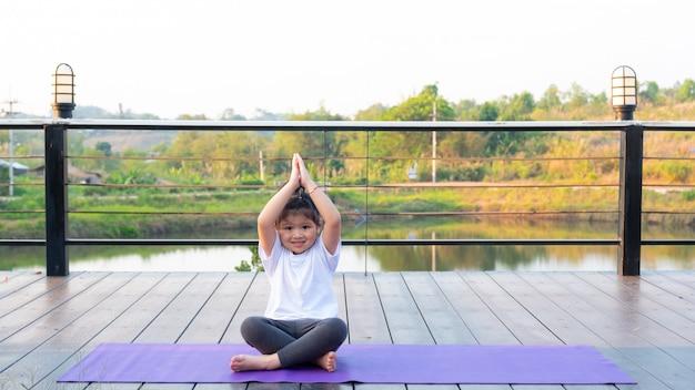 Garota está praticando yoga no rio com vista para a selva durante o retiro de férias