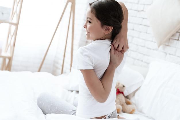 Garota está segurando as mãos atrás das costas.