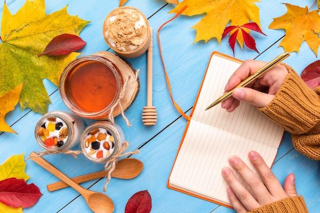 Garota está segurando um caderno na mesa de outono.