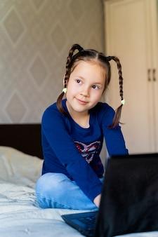 Garota está sentada na cama ao lado do laptop e desvia o olhar