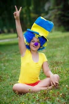 Garota está sentado na grama em peruca de palhaço e chapéu
