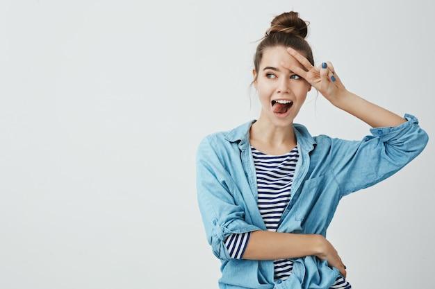 Garota estar do lado positivo o tempo todo. retrato de mulher atraente alegre com penteado de coque segurando sinal v na testa, saindo da língua e olhando de lado, fazendo careta engraçada e bonita