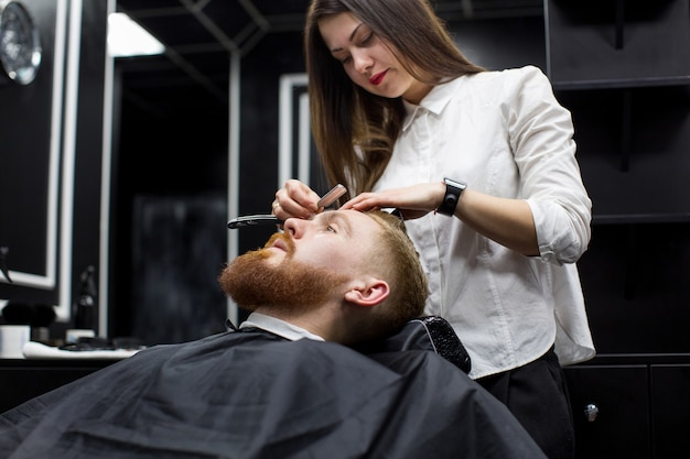 Garota estilista faz a barba de homem em barbearia