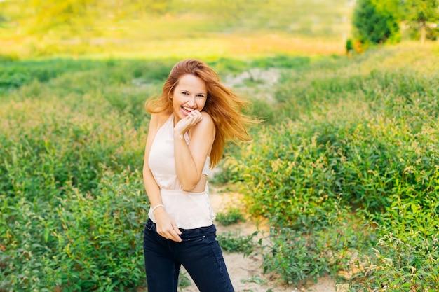 Garota estilosa ri com sinceridade e segura a mão no rosto e olha para as lentes da câmera