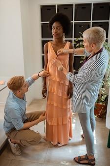 Garota estilosa usando brincos grandes e um vestido laranja estiloso enquanto sorri e desvia o olhar