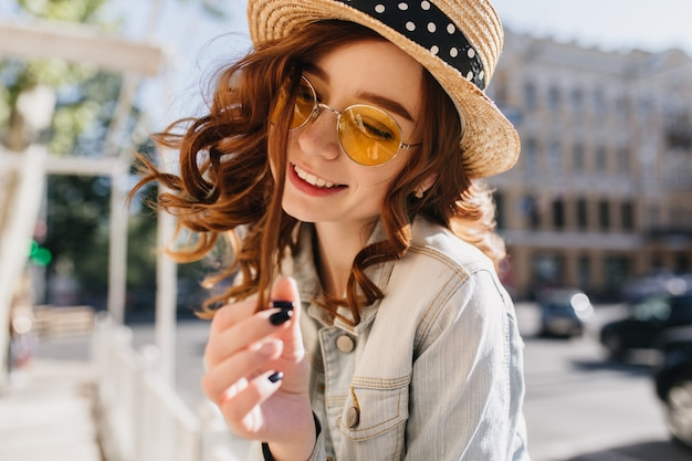 Garota europeia alegre brincando com seu cabelo ruivo com um sorriso. tiro ao ar livre de feliz senhora ruiva com chapéu de verão, posando na rua.