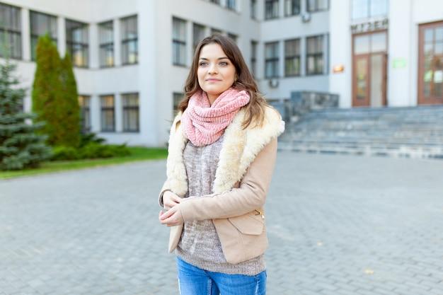 Garota europeia anda pelas ruas com prédios de escritórios.