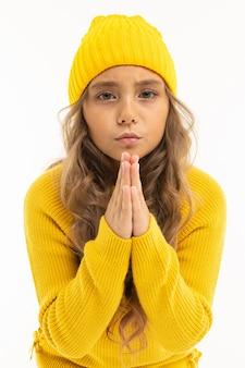 Garota européia atraente com um chapéu e uma jaqueta amarela cruzou as mãos na frente de si mesma em uma parede branca