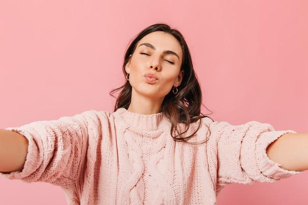 Garota européia bronzeada de olhos fechados manda beijo para a câmera. a senhora de suéter rosa quer abraços.