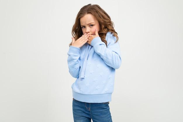 Garota européia em um capuz azul cobriu a boca em uma parede branca com espaço em branco