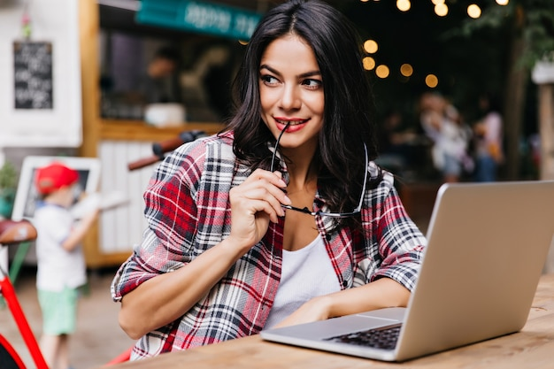 Garota européia esperta posando divertidamente com óculos e laptop. mulher encantadora com cabelo preto olhando ao redor enquanto usa o computador.