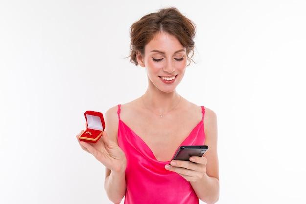 Garota europeia feliz com uma caixa com um anel de casamento escreve uma mensagem por telefone conte a notícia para a amiga em uma parede branca