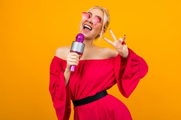 Garota européia liderando o evento em um vestido vermelho com ombros nus, com um microfone nas mãos