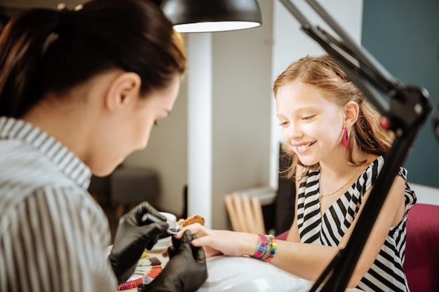 Garota excitada. adolescente fofa e radiante se sentindo animada por vir ao salão de manicure pela primeira vez