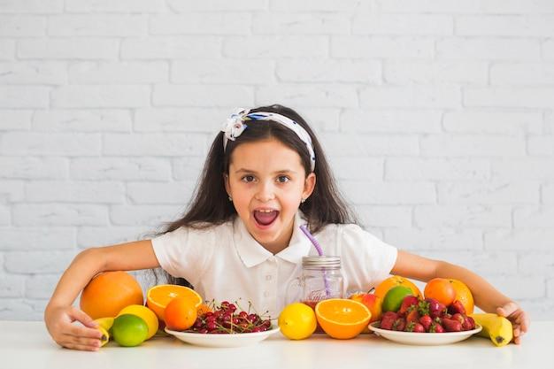 Garota excitada, cobrindo as frutas orgânicas frescas coloridas