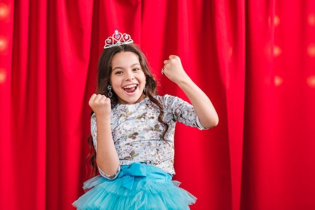 Garota excitada em pé na frente da cortina vermelha