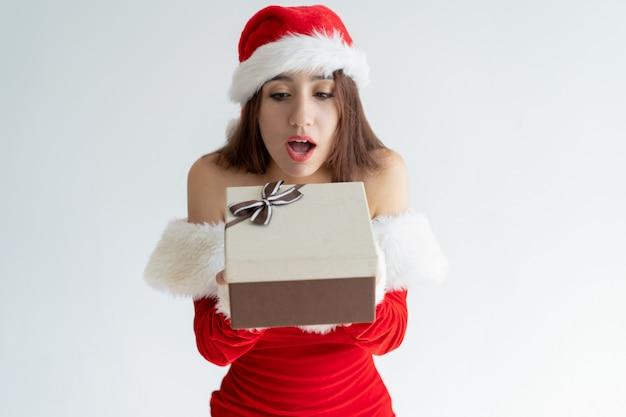 Garota excitada no chapéu de papai noel, adivinhando o que na caixa de presente