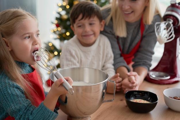 Garota experimentando pasta de açúcar durante o cozimento com a família