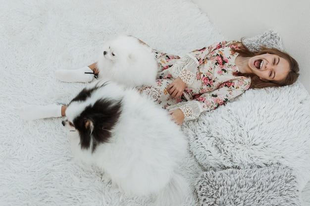 Garota extremamente feliz com dois cachorros