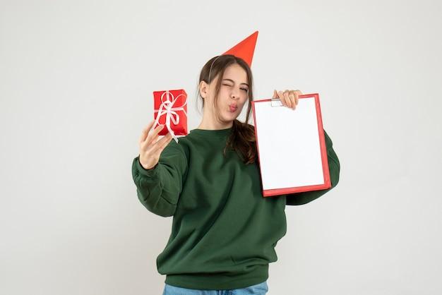 Garota exultante de frente com boné de festa segurando o presente e o documento de natal