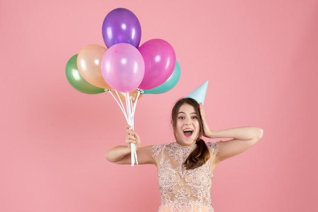 Garota exultante de frente com chapéu de festa segurando balões coloridos
