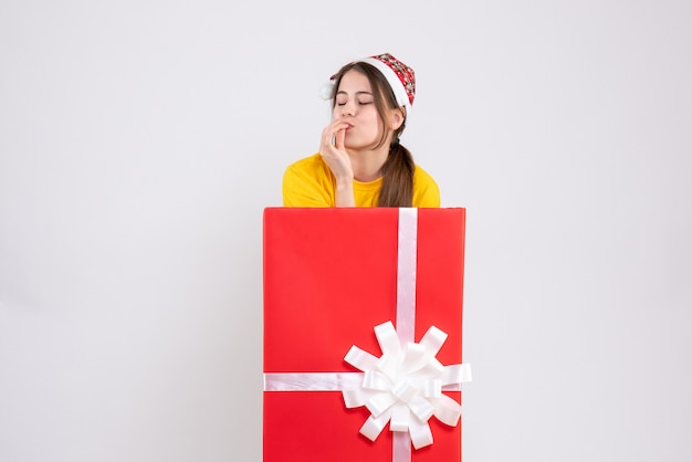 Garota exultante de frente com chapéu de papai noel atrás de um grande presente de natal