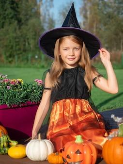 Garota fantasiada de bruxa sentada com abóboras no terraço de madeira